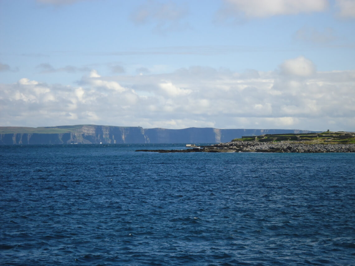 View of the cliffs of Moher and Inisheer, one of the Aran Islands. This picture was taken under difficult conditions, balancing on a swaying boat and avoiding vomiting fellow students.