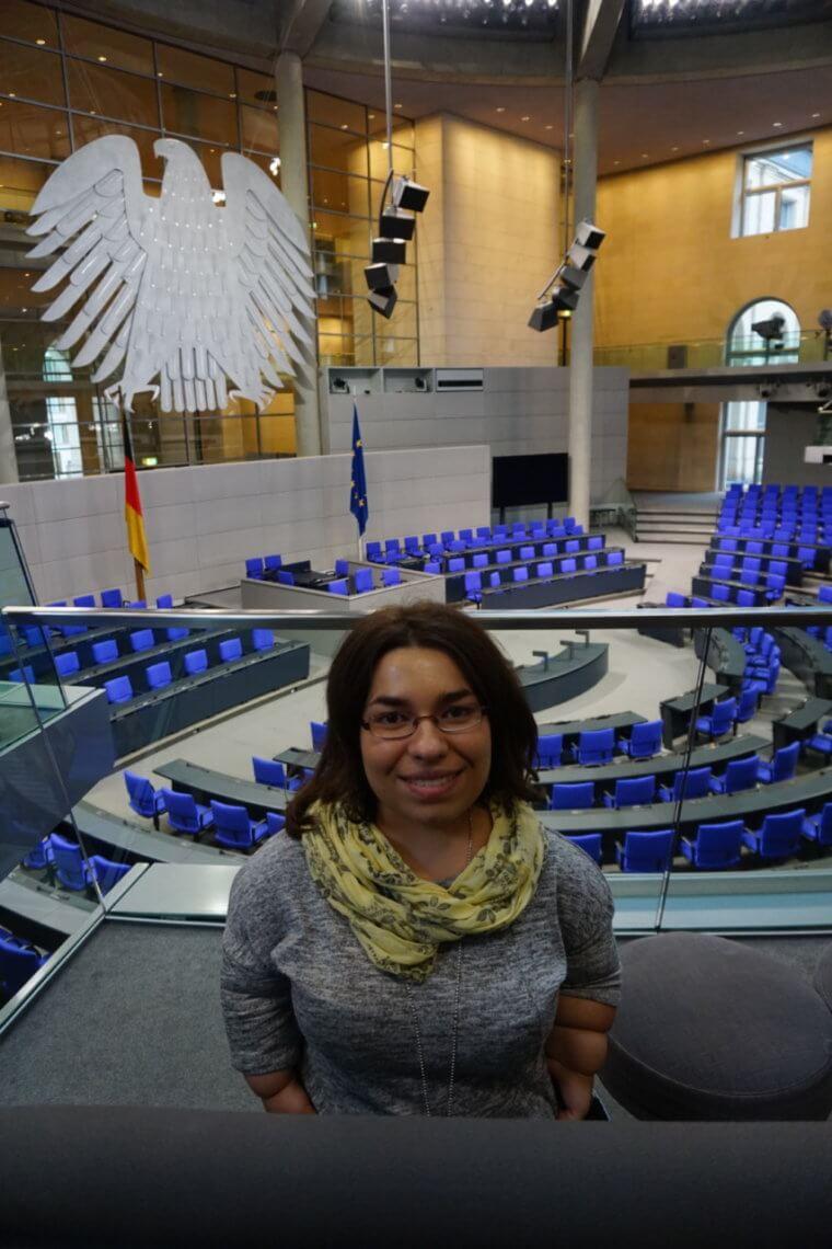 Autorin auf einer Tribüne und im Hintergrund der Plenarsaal des Bundestag