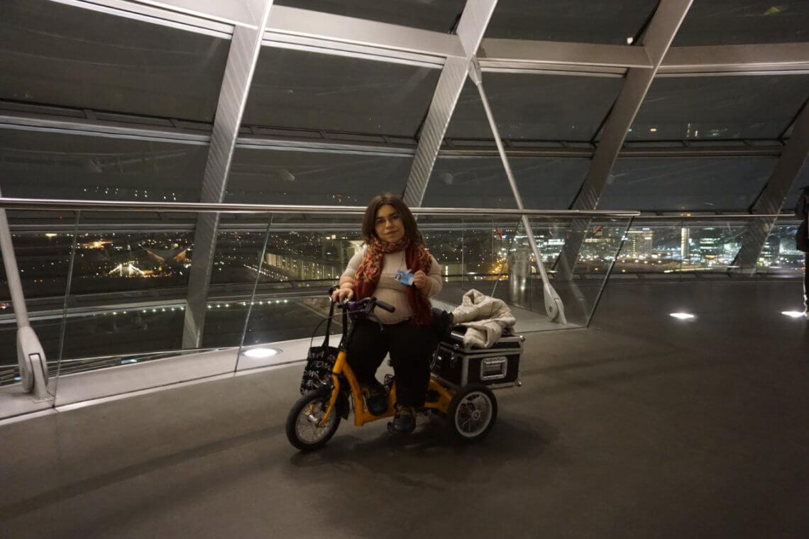 Autorin auf eine Tribüne und im Hintergrund der Plenarsaal des Bundestags