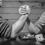 Zwei Männer spielen gegeneinander Arm drücken. Es geht um Geld. wie immer, wird es einen Gewinner und einen Verlierer geben.