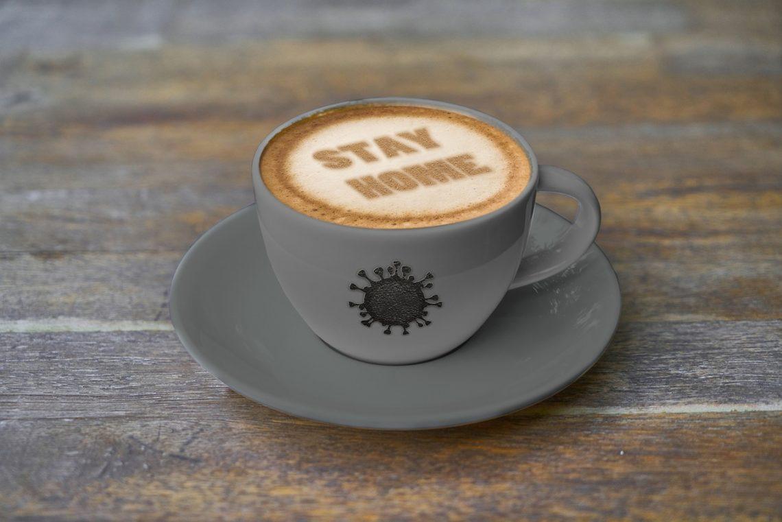 """Eine Tasse Cappuccino - auf dem Milchschaum steht mit Kakao """"Stay Home"""""""