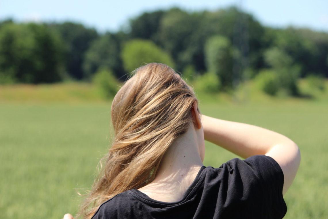 Ein blondes Mädchen befindet sich draußen, man sieht nur die Rückseite. Im Hintergrund sieht man unscharf ein Weizenfeld sowie einen Wald.