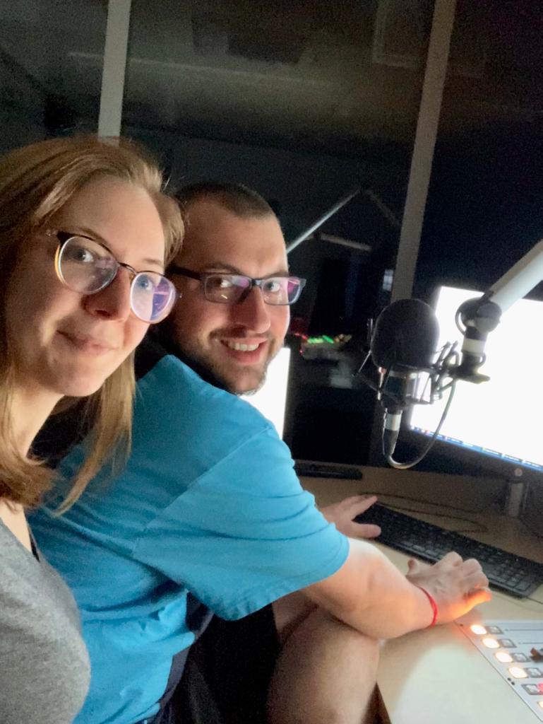 Jasmin Assauer und Jens Foto stehen vor einem Mikrofon in einem Radiostudio und schauen beide in die Kamera.
